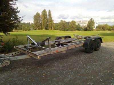 Úprava přívěsného vozíku k přepravě 8m, motorové,  lodi. Úpravy: stabilizační konstrukce, výškově stavitelné podpěrné válečky, posunuté nápravy, protažení světelné lišty, úprava uchycení blatníků.  Celé v žárovém zinku.